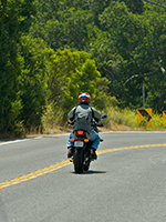 Image of a motorcycle riding down an open road